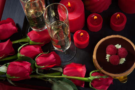 candle light table setting: Celebration tray for Valentines Day - Champagne, chocolate raspberry cake, candles, and red roses.
