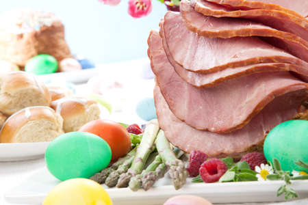 jamon: Todo al horno miel lonchas de jamón con frambuesas frescas, espárragos, huevos teñidos Ester, pastel de Pascua y bollos cruzados. Flores de primavera.