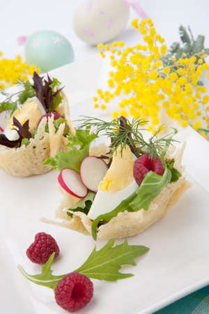 appetizers: Parmesan baskets filled with fresh garden salad, hard-boiled eggs, and fresh raspberries. Easter decorated eggs, spring flowers, holiday theme. Over white.