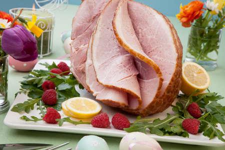 jamon: Pascua tem�tica preparada jam�n rebanado miel y frambuesa fresca, r�cula, limones, huevos Ester decoraci�n. flores de la primavera y el vino rosado.