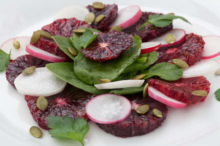 pumpkin seeds: Closeup of a plate of juicy salad with blood oranges, radish, spinach, and pumpkin seeds. Citrus dressing.