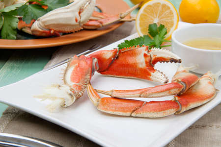 dungeness: Assorted Dungeness crab legs with butter mustard sauce and fresh lemons. Stock Photo