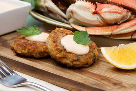 Drei Krabbenkuchen Vorspeise mit scharfer Soße und frischer Petersilie. Dungeness Krabbe im Hintergrund.