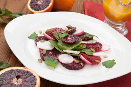 CITRICOS: Primer plano de un plato de ensalada jugosa con naranjas de sangre, rábano, espinaca, y las semillas de calabaza. Citrus vestidor.