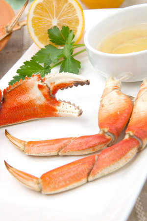 Assorted Dungeness crab legs with butter mustard sauce and fresh lemons. Stock Photo