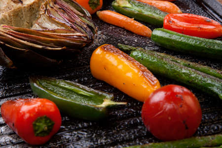 grilled vegetables: Assorted grilled vegetables - zucchini, asparagus, artichokes, mini pepper, jalapeno, tomatoes, and carrots - on griddle. Stock Photo