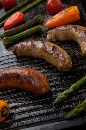 griddle: Summer grill - grilled sausages and assorted grilled vegetables - asparagus, mini pepper, and tomatoes - on griddle.