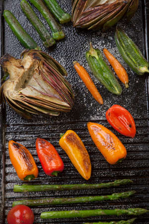 griddle: Assorted grilled vegetables - zucchini, asparagus, artichokes, mini pepper, jalapeno, tomatoes, and carrots - on griddle. Stock Photo