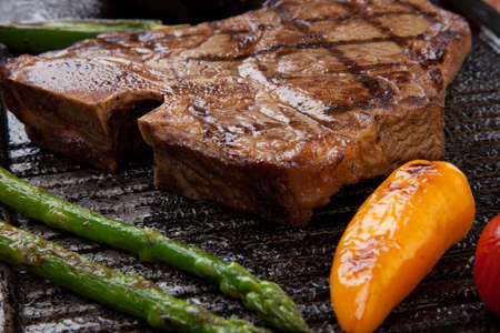 tbone: Summer grill - grilled sausages and T-bone steak - on griddle. Stock Photo