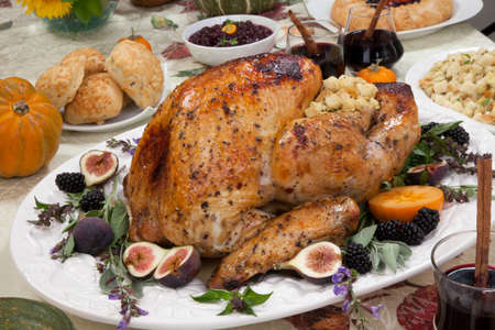 Dinner table with roasted Thanksgiving turkey is ready to feast. Turkey is garnished with fresh figs, blackberries, sage, and basil. Sided dishes, pumpkinks, flowers, and red wine cocktails.