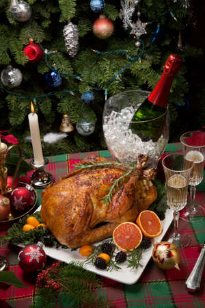 roasted turkey: Roasted turkey with fresh fruits, flutes of champagne, Christmas tree, candles, and decorations