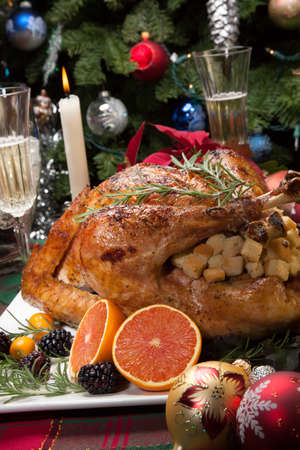 christmas meal: Roasted turkey with fresh fruits, flutes of champagne, Christmas tree, candles, and decorations