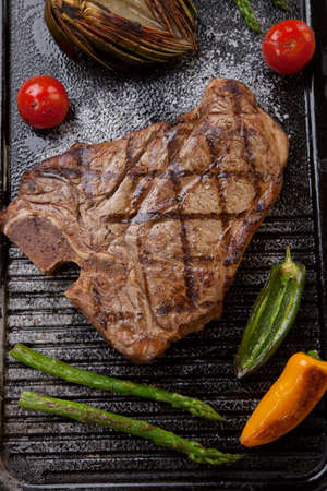 griddle: Summer grill - grilled T-bone steak and assorted grilled vegetables - asparagus, mini pepper, and tomatoes - on griddle. Stock Photo