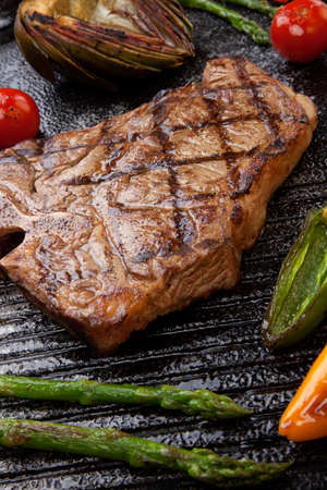 Summer grill - grilled T-bone steak and assorted grilled vegetables - asparagus, mini pepper, and tomatoes - on griddle. Stock Photo