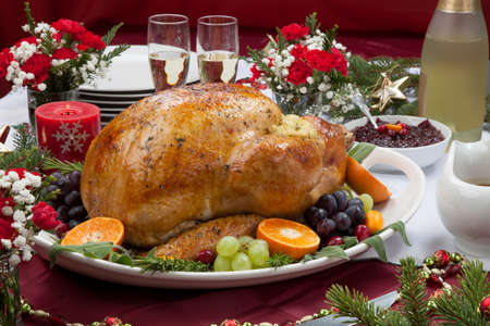 poultry: Roasted herb rubbed turkey garnished with fresh grapes, oranges, and cranberry is ready for Christmas dinner. Ornaments, Champagne, candles, and other Christmas decorations on feast table.