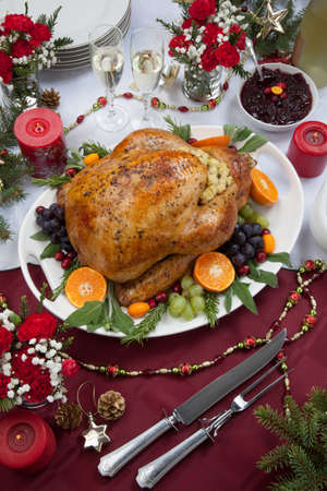 feast: Roasted herb rubbed turkey garnished with fresh grapes, oranges, and cranberry is ready for Christmas dinner. Ornaments, Champagne, candles, and other Christmas decorations on feast table.