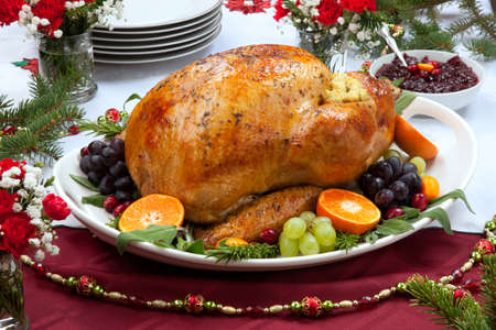 Roasted herb rubbed turkey garnished with fresh grapes, oranges, and cranberry is ready for Christmas dinner. Ornaments, Champagne, candles, and other Christmas decorations on feast table. Reklamní fotografie