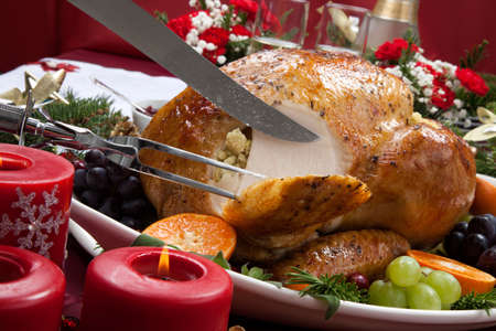 feast: Carving roasted herb rubbed turkey garnished with fresh grapes, oranges, and cranberry is ready for Christmas dinner. Ornaments, Champagne, candles, and other Christmas decorations on feast table. Stock Photo