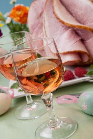 Easter themed prepared sliced honey ham and fresh raspberry, arugula, lemons, Ester eggs decoration. Spring flowers and pink wine.