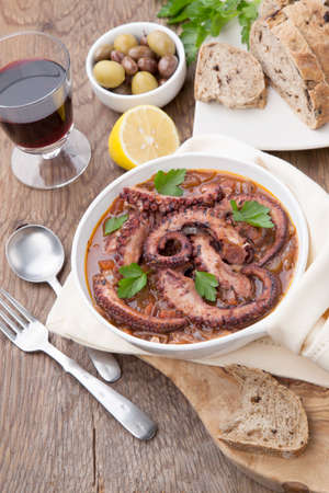 Bowl of delicious octopus and red wine stew - traditional Mediterranean dish. Fresh bread, olives, and red wine.