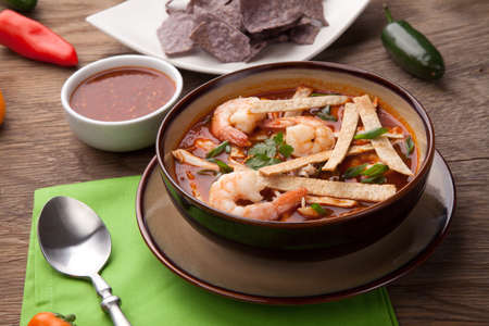 soup bowl: Bowl of hot delicious shrimp tortilla soup garnished with green onion, fresh cilantro, and salsa.