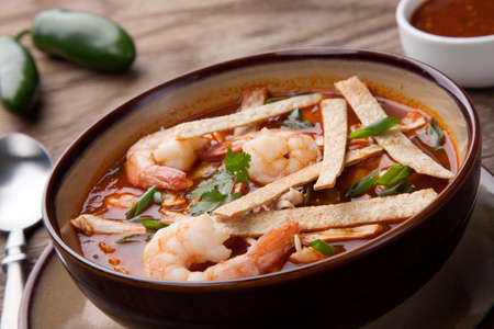 Bowl of hot delicious shrimp tortilla soup garnished with green onion, fresh cilantro, and salsa.