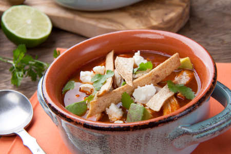 Bowl of hot delicious spicy chicken tortilla soup garnished with crumbled queso fresco cheese, diced avocado, and fresh cilantro.