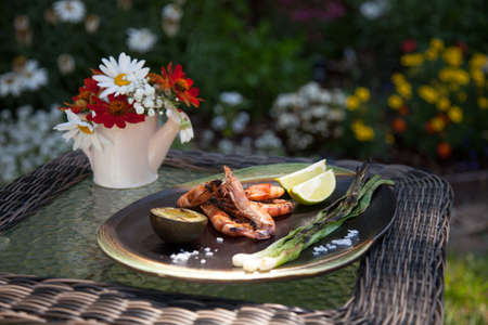 Plate of grilled shrimps, avocado, and scallions. Served with lime ans sea salt. Outside dinner in a garden.