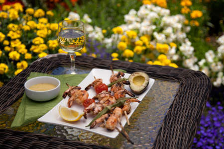 Plate of grilled shrimps skewers with grilled vegetables and avocado. Served with lemon and lemon butter sauce. Outside dinner in a garden.