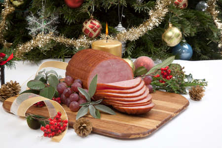 Roasted ham with fresh thyme for Christmas party. XMas tree in the background, surrounded by ornaments. Rustic style. Zdjęcie Seryjne