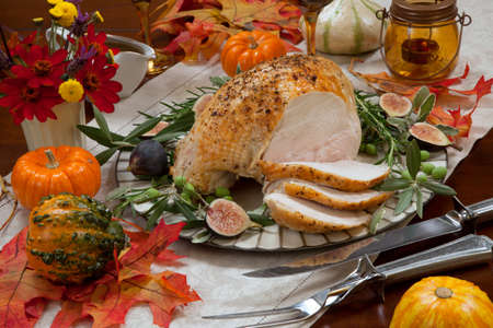 Carving whole roasted turkey breast, Mediterranean style, garnished with fresh figs, olives, and herbs. Surrounded by pumpkins, candles, red wine, and ornaments. Thanksgiving theme.