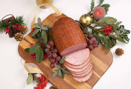 Roasted ham with fresh thyme for Christmas party. XMas tree in the background, surrounded by ornaments. Rustic style. Stock Photo