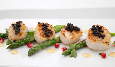 Close up of delicious appetizer scallops with black caviar. Garnished with asparagus, pomegranate seeds, microgreens, and sauce. Elite food. Stock Photo