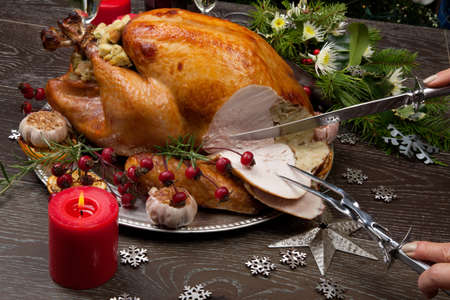 Carving rustic style roasted Christmas turkey garnished with roasted garlic, lemon, and rosehips. Surrounded with rustic Christmas ornaments, candles, wine, flowers, and Christmas tree in the background. Stock Photo