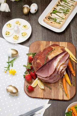 Delicious spicey roasted ham with deviled eggs, asparagus parmesan pastry, butternut squash with green peas, baby carrots, strawberries, and Easter decoration. Zdjęcie Seryjne