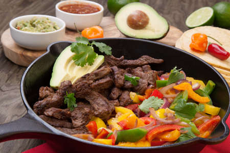 Beef fajitas with bell pepper, onion, and avocado in cast iron skillet ready to be served.