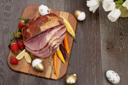 Delicious spicey roasted ham with deviled eggs, asparagus parmesan pastry, butternut squash with green peas, baby carrots, strawberries, and Easter decoration. Stock Photo