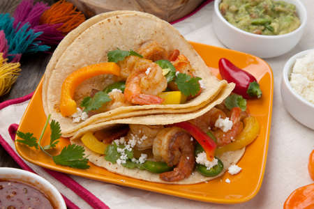 Two shrimp fajitas with bell pepper, onion, and jalapeno in a plate and shrimp fajitas in a cast iron skillet ready to be served. Guacamole, salsa, and tortillas. Stock Photo