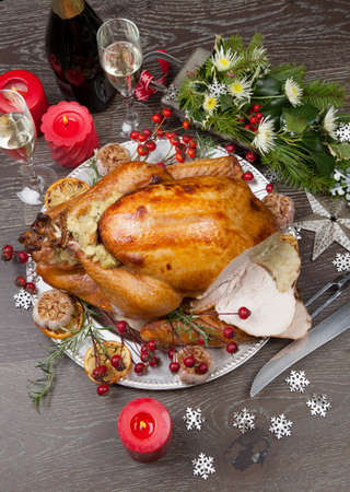 Carving rustic style roasted Christmas turkey garnished with roasted garlic, lemon, and rosehips. Surrounded with rustic Christmas ornaments, candles, wine, flowers, and Christmas tree in the background. Standard-Bild