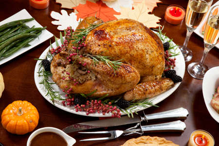 Roasted pepper turkey for Thanksgiving, garnished with pink pepper, and fresh rosemary twigs on a dinner table decorated with mini pumpkins, beans, carrots, baked potato, pie, cranberry relish, gravy, flowers, candles, and flutes of champagne. Stok Fotoğraf