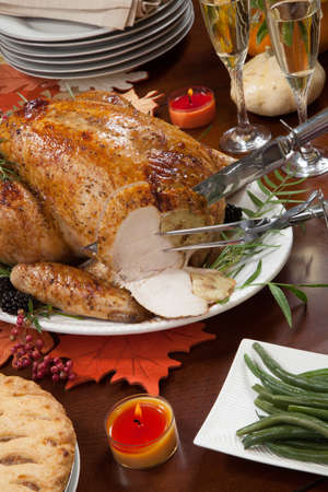 Carving roasted pepper turkey for Thanksgiving, garnished with pink pepper, black berry, and fresh rosemary twigs on a dinner table decorated with mini pumpkins, beans, carrots, baked potato, pie, cranberry relish, gravy, flowers, candles, and flutes of champagne.