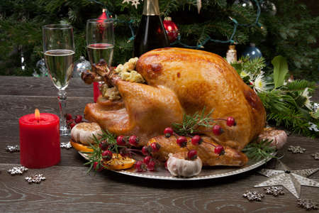 Rustic style roasted Christmas turkey garnished with roasted garlic, lemon, and rosehips. Surrounded with rustic Christmas ornaments, candles, wine, flowers, and Christmas tree in the background. Stock Photo