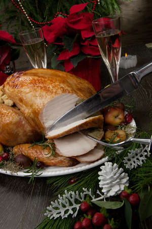 Carving garnished roasted Christmas turkey with grab apples, sweet chestnut, cranberry, Christmas ornaments, candles, and pine cones.