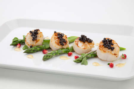 Close up of delicious appetizer scallops with black caviar. Garnished with asparagus, pomegranate seeds, microgreens, and sauce. Elite food. Фото со стока