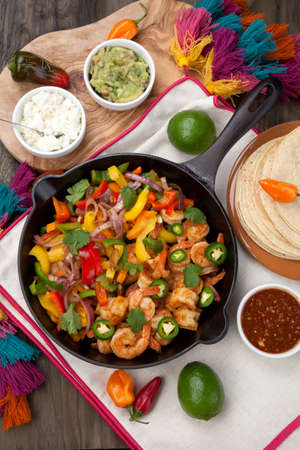 Shrimp fajitas with bell pepper, onion, and jalapeno in cast iron skillet ready to be served. Guacamole, salsa, and tortillas.