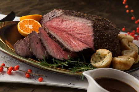 Peppercorn roast beef with herbed Yorkshire puddings and gravy. Stock Photo