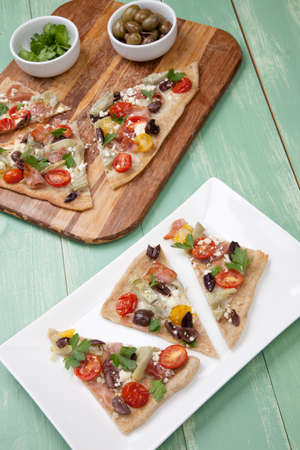 Closeup of a plate with few pieces of home made Mediterranean flatbread made with prosciutto, artichoke, cherry tomatoes, feta cheese, and olives. Garnished with parsley leafs. Фото со стока