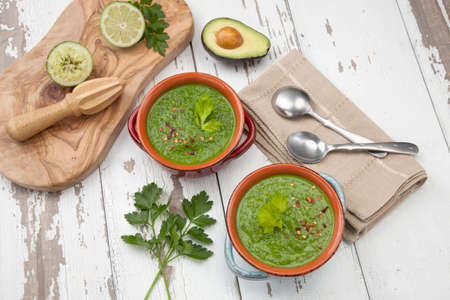 Two bowls of green gazpacho soup with boiled eggs - appetizer for Easter brunch. Easter eggs and flowers.