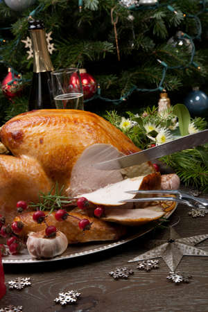 Carving rustic style roasted Christmas turkey garnished with roasted garlic, lemon, and rosehips.