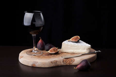 Closeup of Brie cheese with fresh black figs and glass of red wine - great snack for wine tasting. Over black background. Contemporary appetizers series.